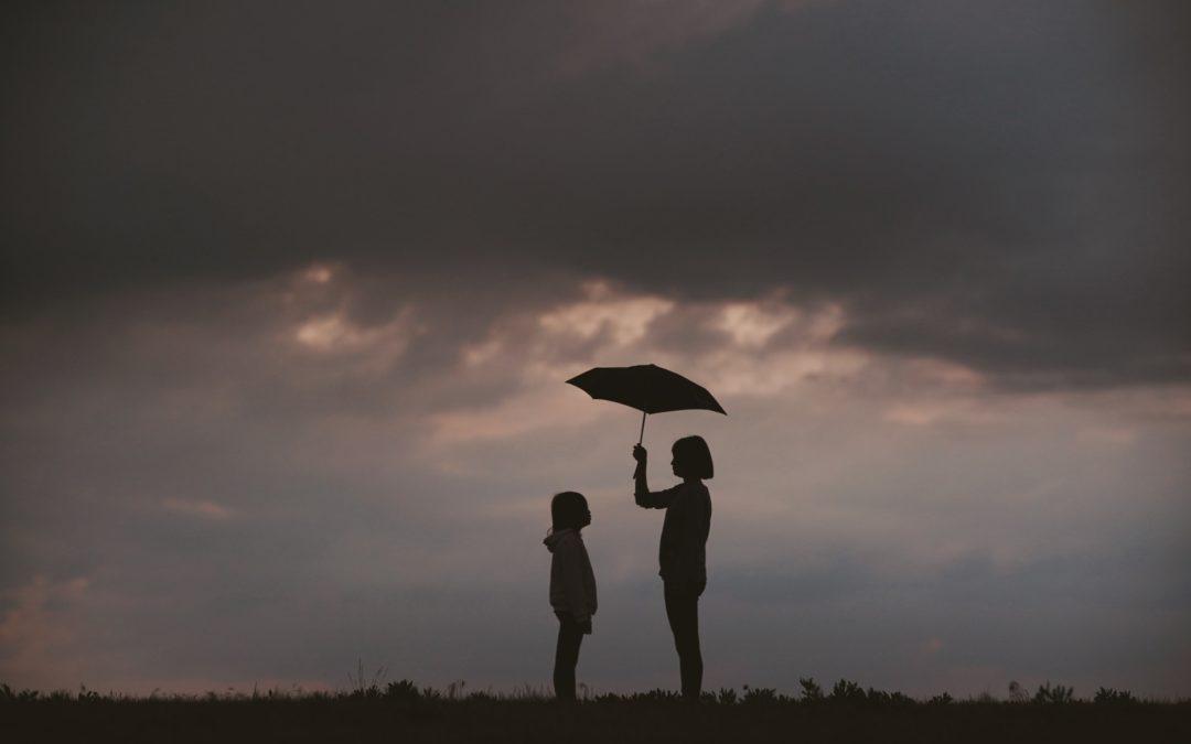 2 share an umbrella in a storm