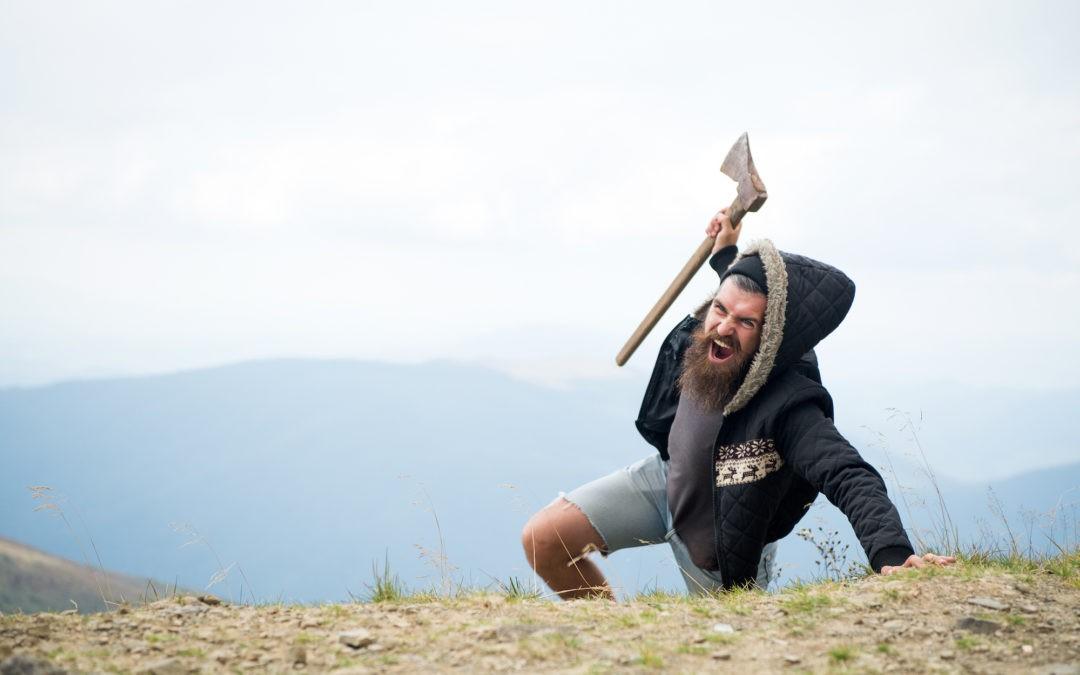 man climbing a hill with an axe